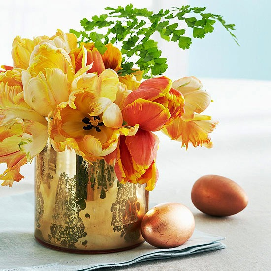 Gold plated, polished vase with flowers of yellow and orange spring